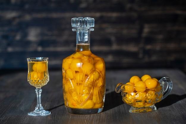 Domowej roboty nalewka z żółtej wiśni śliwki w kryształowej butelce i kieliszek do wina na drewnianym stole, ukraina, z bliska. koncepcja napojów alkoholowych jagód