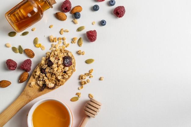 Domowej roboty naturalna granola z miodem, jagodami i dokrętkami w drewnianej łyżce na bielu