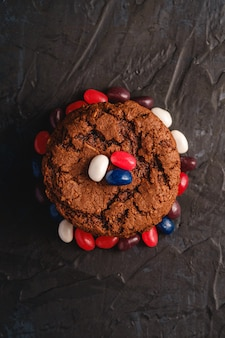 Domowej roboty owsiane czekoladowe ciastka brogują z zbożem z soczystymi galaretowymi fasolami na textured ciemnej czerni powierzchni, odgórny widok