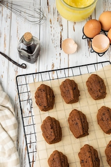 Domowej roboty piekarni czekoladowe madeleine ciastka na chłodzącym stojaku z składnikami i naczyniami na nieociosany drewnianym