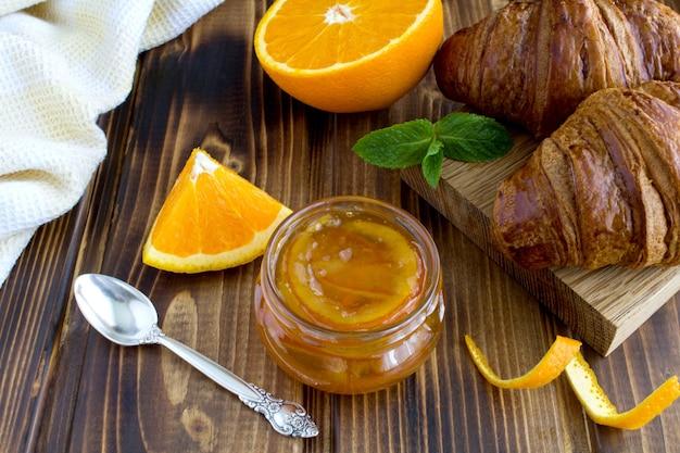 Domowej roboty pomarańczowa marmolada w szklanym słoju i rogaliki na brązowym tle drewnianych