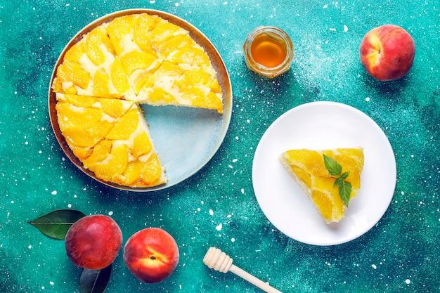 Domowej roboty pyszna francuska tarta deserowa z brzoskwiniami.