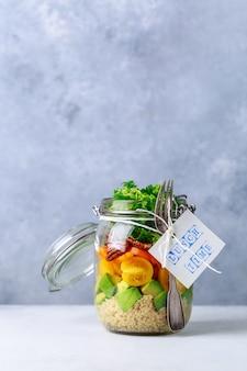 Domowej roboty sałatka w szklanym słoju z quinoa i warzywami z etykietka lunchu czasem żadny klingeryt i bierze oddalonego pojęcie