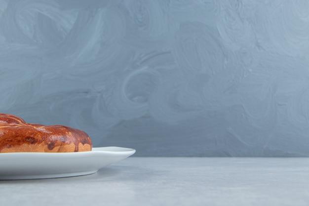 Domowej roboty słodka bułka na białym talerzu.