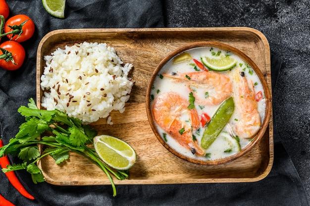 Domowej roboty tom kha gai. zupa z mleka kokosowego w misce. tajskie jedzenie. czarna powierzchnia. widok z góry