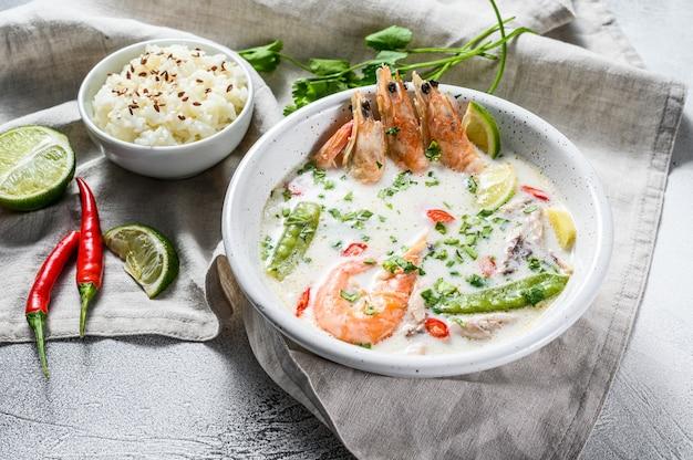 Domowej roboty tom kha gai. zupa z mleka kokosowego w misce. tajskie jedzenie. szara powierzchnia. widok z góry