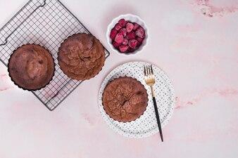 Domowej roboty upieczone ciasta na blasze do pieczenia i talerze z mrożonych malin miska na różowym tle