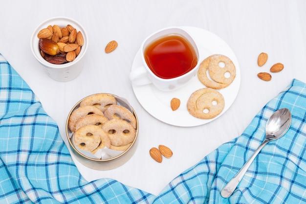 Domowej roboty uśmiechów ciastka z filiżanką czarna herbata na białym drewnie