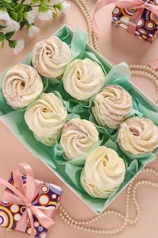 Domowej roboty zefir lub marshmallows w pudełku na różowej powierzchni, odgórny widok