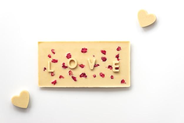 Domowy baton z białej czekolady nerkowca z malinami z napisem