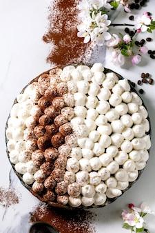Domowy bezglutenowy tradycyjny włoski deser tiramisu posypany kakao w proszku ozdobiony kwitnącą jabłonią i ziarnami kawy na białym marmurowym tle. widok z góry, układ płaski. skopiuj miejsce