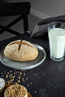 Domowy bochenek świeżo upieczonego zielonego chleba gryczanego i ekologicznego mleka gryczanego. ceramiczna, lniana serwetka. nieszkodliwe, zdrowe, bezglutenowe, zdrowe wypieki dla wegan. alternatywny chleb i mleko wegetariańskie