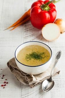 Domowy bulion w białej misce na serwetce z koperkiem i świeżymi warzywami na drewnianym stole. pojęcie zdrowego odżywiania.