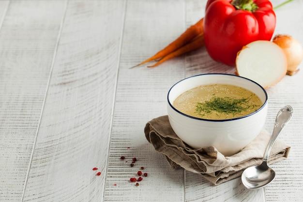 Domowy bulion w białej misce na serwetce z koperkiem i świeżymi warzywami na drewnianym tle. pojęcie zdrowego odżywiania. skopiuj miejsce.