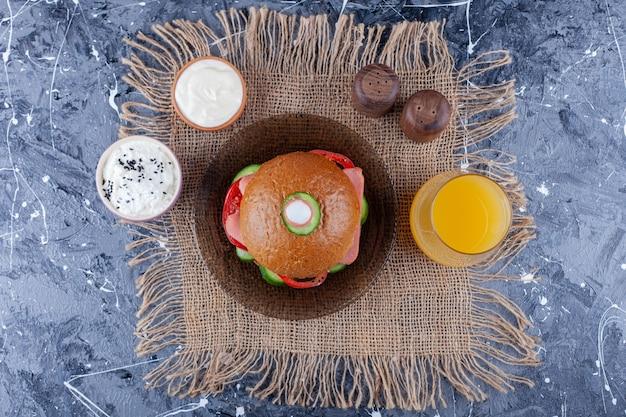 Domowy burger na talerzu obok szklanki soku na jutowej serwetce na niebiesko.