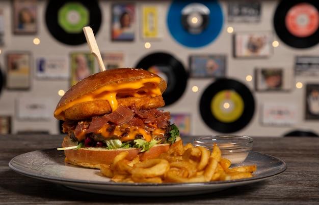 Domowy burger wołowy z panierowanym serem brie, sosem cheddar, szynką serrano z frytkami na drewnianym stole. odosobniony obraz.