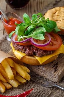 Domowy burger z frytkami na drewnianym