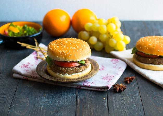 Domowy burger z warzywami i mięsem wołowym na drewnianym stole