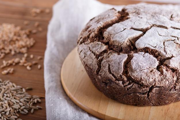 Domowy chleb bez drożdży z pełnymi ziarnami żyta i pszenicy na rustykalne drewniane tła