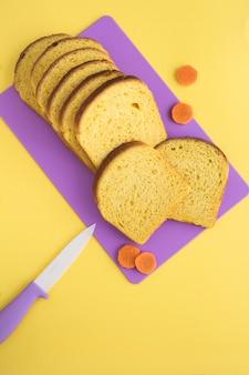 Domowy chleb marchewkowy na fioletowej desce do krojenia na żółtym stole. widok z góry.