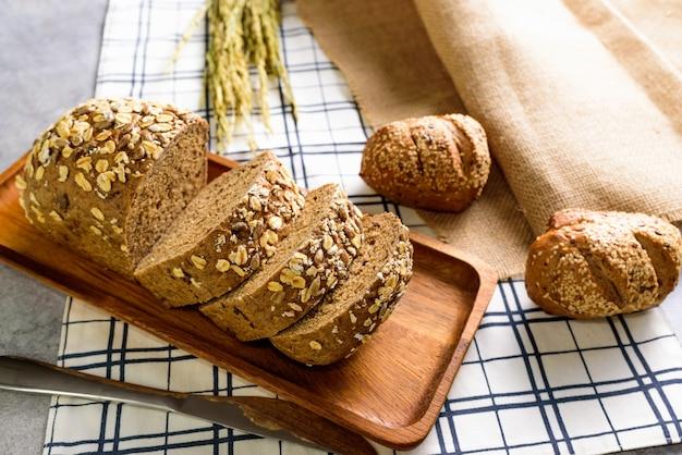 Domowy chleb pełnoziarnisty bochenek chleba żytniego jest cięty i umieszczany na drewnianym talerzu.i umieścić na obrusie.