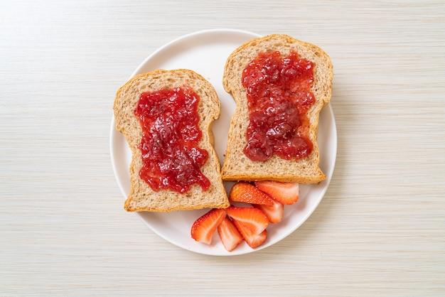 Domowy chleb pełnoziarnisty z dżemem truskawkowym i świeżą truskawką