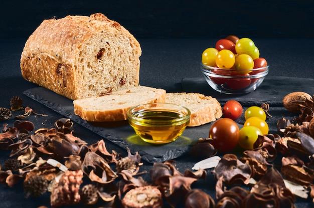 Domowy chleb pomidorowy z kilkoma plasterkami pokrojonymi w łupek, z oliwą z oliwek i miską pomidorów cherry