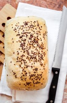 Domowy chleb pszenny z nasionami lnu na stole kuchennym płaski, leżący widok z góry