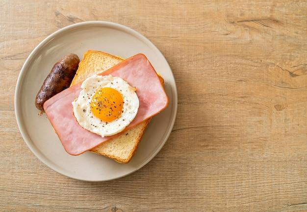 Domowy chleb tostowy ser posypany szynką i jajkiem sadzonym z kiełbasą wieprzową na śniadanie