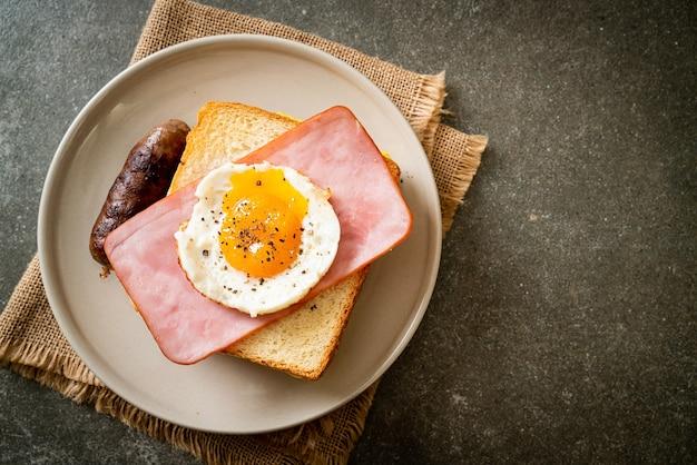 Domowy chleb tostowy z serem z szynką i jajkiem sadzonym z kiełbasą wieprzową na śniadanie
