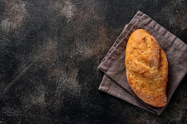 Domowy chleb z nasionami na drewnianym stojaku, mąka pszenna i kłosy na brązowym starym stole betonowym.