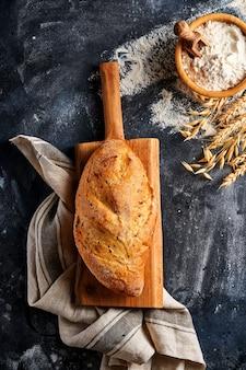 Domowy chleb z nasionami na drewnianym stojaku, mąka pszenna i kłosy na szarym starym stole betonowym.