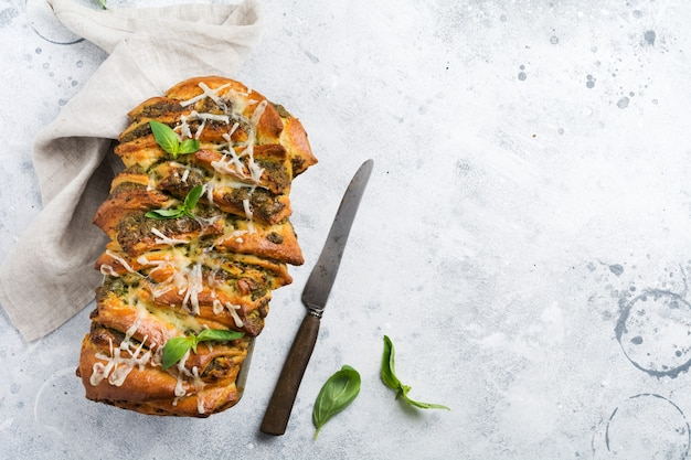 Domowy chleb z pesto pleciony przyozdobionym listkami bazylii na prostym jasnoszarym betonowym stole. włoski tradycyjny chleb. skopiuj miejsce. widok z góry.