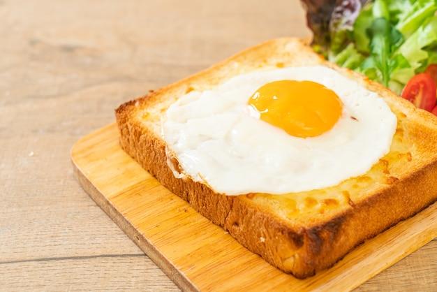 Domowy chleb zapiekany z serem i jajkiem sadzonym na wierzchu z sałatką jarzynową na śniadanie