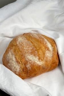 Domowy chleb zawinięty w biały obrus