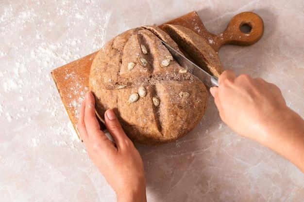 Domowy chleb. zbliżenie kobiece ręce krojenie świeżo upieczonego chleba na marmurowym blacie