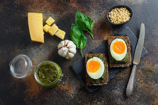 Domowy chlebek panini z zielonym pesto bazyliowym w szklanym słoiku, srebrna łyżeczka