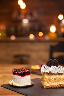 Domowy deser ze świeżymi owocami i pikantną śmietaną na wierzchu. pyszne ciasta bez cukru. smaczne ciasto z biszkoptem na wierzchu. ciasto z kremem cytrynowym w środku