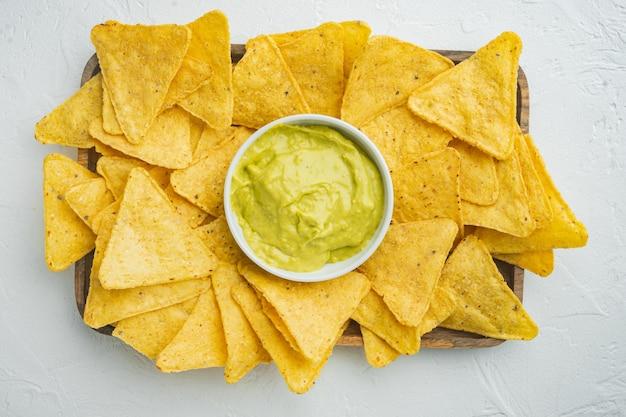 Domowy dip z guacamole i sera z nachos, na białym stole, widok z góry lub flat lay