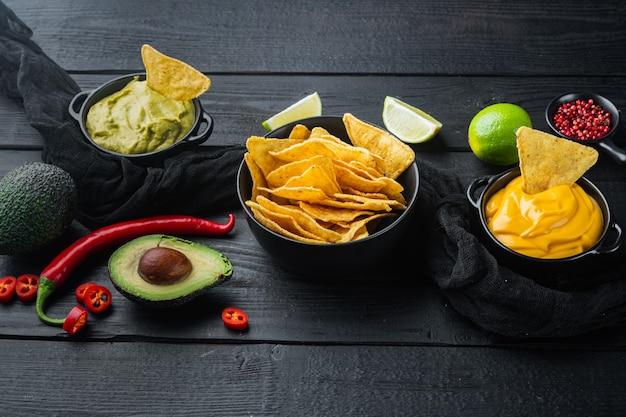 Domowy dip z guacamole i sera z nachos, na czarnym drewnianym stole