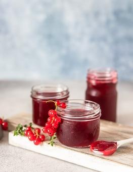 Domowy dżem lub galaretka z czerwonej porzeczki w szklanych słoikach i świeże jagody z czerwonych porzeczek.