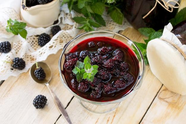 Domowy dżem szklany słoik z jeżyną i miętą na drewnianym stole jagoda zakonserwowana