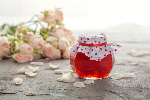 Domowy dżem z płatków róży na stole z bukietem róż.