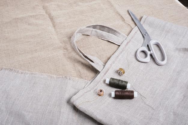 Domowy eko shopper, nożyczki i nici na lnianym materiale widok z góry