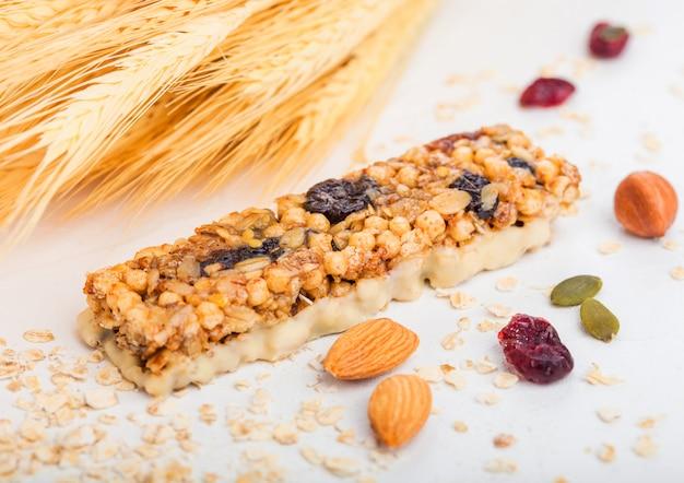 Domowy ekologiczny batonik zbożowy muesli z orzechami i suszonymi owocami na białym tle z owsem i surową pszenicą.