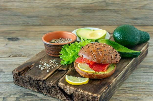 Domowy ekologiczny burger z łososia z pomidorem, roszponką i avogado na talerzu na drewnianym tle. zdrowa żywność ekologiczna.
