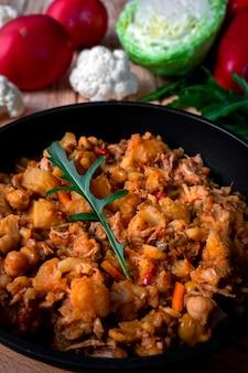 Domowy gulasz mięsny z warzywami, ziemniakami, cebulą, marchewką, kalafiorem, kapustą, papryką z sosem pomidorowym, czosnkiem i ziołami w naczyniu do smażenia na drewnianym stole.