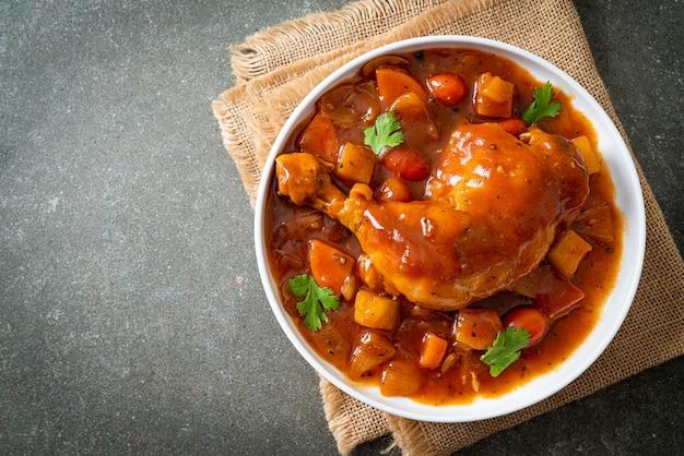 Domowy gulasz z kurczaka z pomidorami, cebulą, marchewką i ziemniakami na talerzu