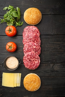 Domowy hamburger. surowe paszteciki wołowe, bułeczki sezamowe z zestawem innych składników, na czarnym drewnianym stole