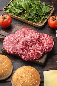 Domowy hamburger. surowe paszteciki wołowe, bułeczki sezamowe z zestawem innych składników, na starym ciemnym drewnianym stole